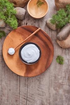 Crème cosmétique et feuilles fraîches sur fond de table en bois