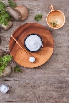Crème cosmétique et feuilles de lavande fraîche sur fond de table en bois blanc