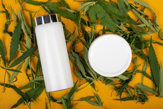 Crème Cosmétique De Marijuana Pour Le Soin De Peau Sur Le Produit De Chanvre De Fond Jaune Photo Premium