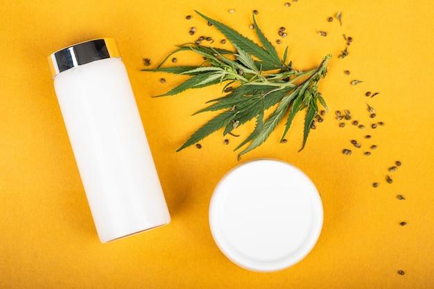 Crème cosmétique de marijuana pour le soin de peau sur le produit de chanvre de fond jaune