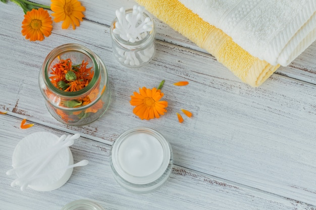 Crème cosmétique naturelle, baume ou pommade, coton, bâtonnets et serviettes au calendula fleurs sèches et fraîches sur une surface claire