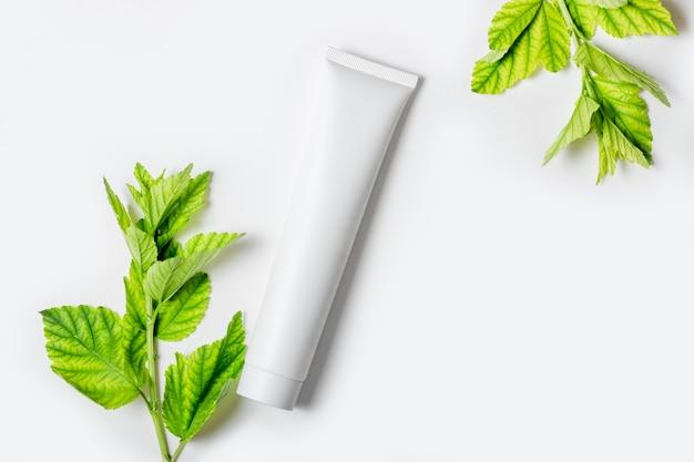 Crème cosmétique pour hydrater et nettoyer le visage. crème ou masque facial en tubes blancs et feuilles de plantes naturelles. bouteille blanche avec espace vide