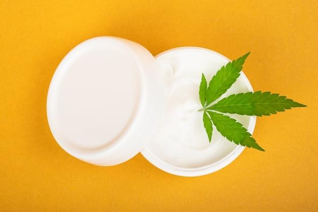 Crème cosmétique pour lutter contre les rides de la peau avec du cannabis sur fond jaune.