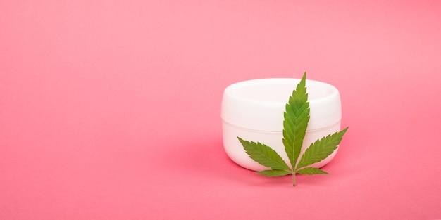 Crème cosmétique pour les soins de la peau et feuille de marijuana verte.