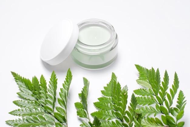 Crème cosmétique en récipient et feuilles vertes fraîches sur blanc. spa fait maison, pot de crème bio, cosmétiques naturels, produits de beauté