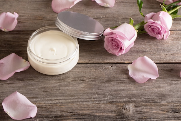 Crème cosmétique avec des roses roses sur une vieille table en bois