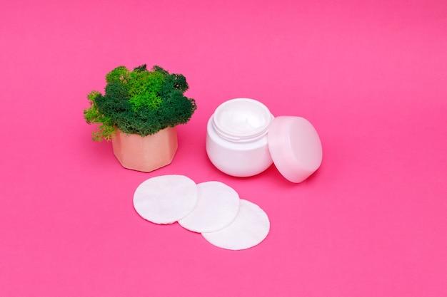 Crème, disques de coton sur une table rose