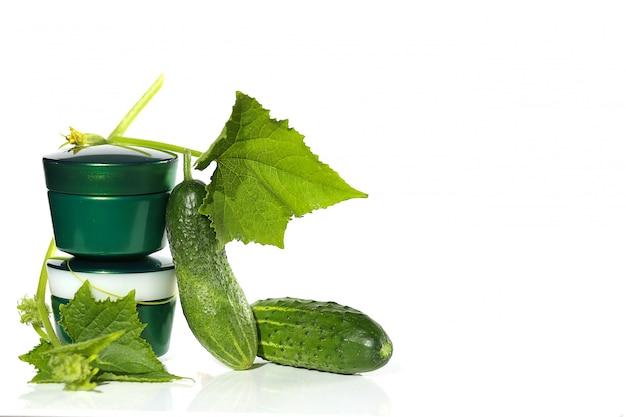 Crème à l'extrait de concombre. crème de concombre dans un pot vert et concombre vert frais avec une feuille. concept de cosmétiques naturels botaniques