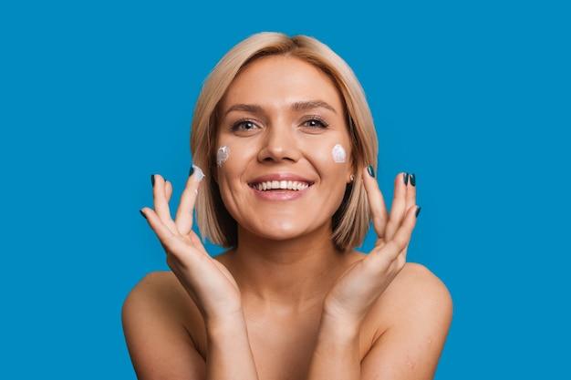 Crème sur fond bleu visage beauté soins de la peau soins des cheveux fille beauté soins du visage