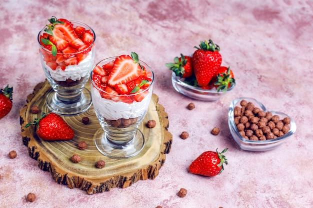 Crème fouettée et bagatelle aux fraises avec du miel et des céréales.