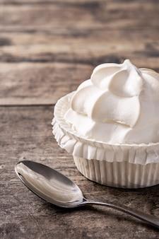 Crème fouettée meringuée sur table en bois