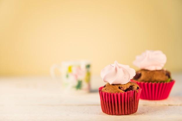 Crème fouettée sur des muffins dans le porte-papier rouge