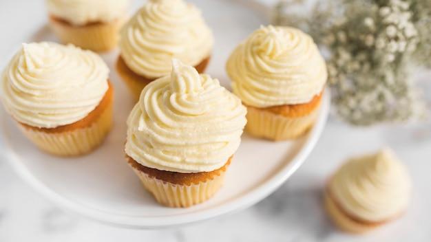 Crème fouettée sur des muffins sur un support de gâteau