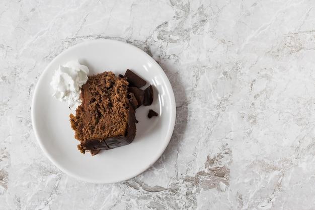 Crème fouettée et rondelle de gâteau sur une assiette sur le comptoir de marbre