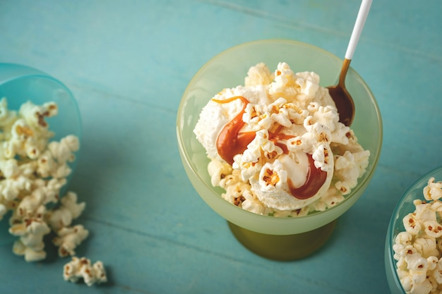 Crème glacée au caramel et pop-corn, fond bleu, espace copie