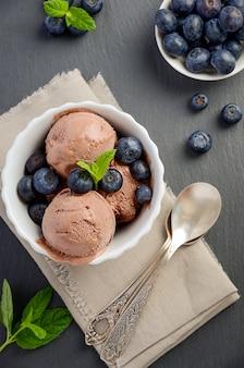 Crème glacée au chocolat avec des bleuets sur fond d'ardoise noire vue de dessus plat lay