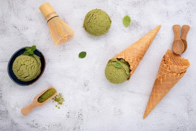 Crème glacée au thé vert matcha avec cornet gaufré et feuilles de menthe sur fond de pierre blanche.