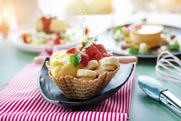 La crème glacée aux fruits, banane et fraise dans un panier à gaufres, une lumière floue.