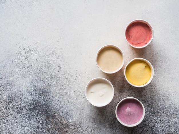 Crème glacée aux fruits frais de différentes couleurs dans des gobelets en papier sur un fond gris. vue de dessus. espace de copie