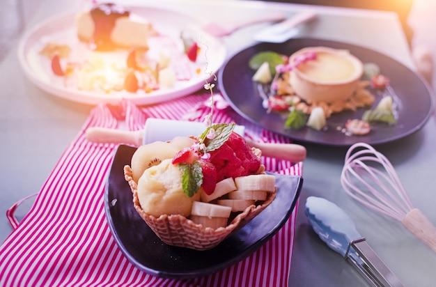 La crème glacée aux fruits mélangés dans une tasse à gaufres posée sur un plat noir avec une lumière floue
