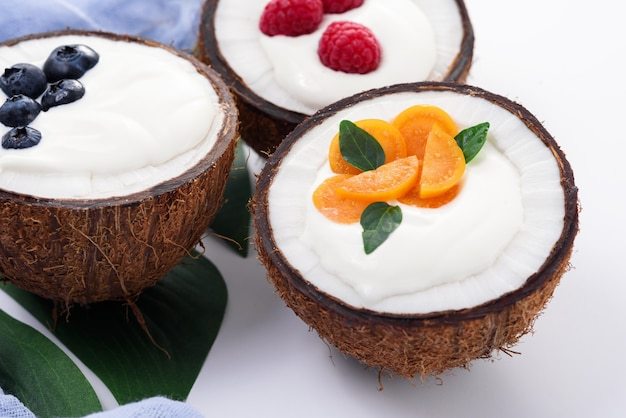 Crème glacée aux fruits rouges dans des bols de noix de coco, milkshake sur blanc