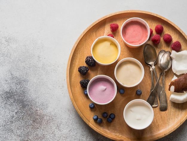 Crème glacée de baies fraîches de différentes couleurs dans des gobelets en papier et baies diverses sur un plateau en bois rond sur un fond gris. vue de dessus. espace de copie