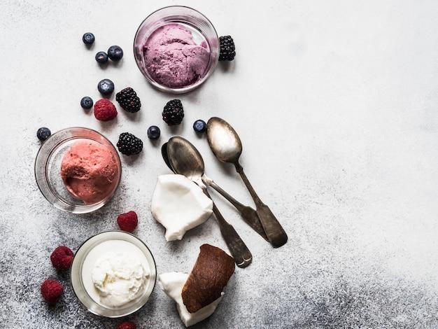 Crème glacée de baies fraîches de différentes couleurs dans le verre, les baies et les cuillères en métal sur un fond gris. vue de dessus. espace de copie