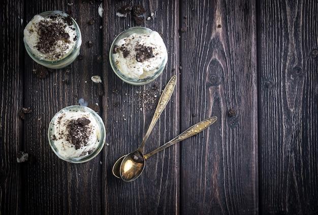 Crème glacée avec des biscuits au chocolat dans des bocaux en verre. style rustique.