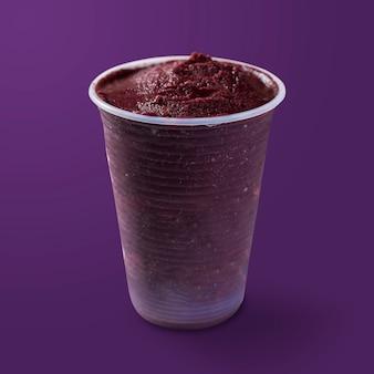 Crème glacée brésilienne aux baies d'açai et congelées sur une tasse en plastique. isolé sur fond violet. vue de face du menu d'été.