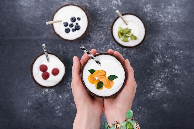Crème glacée dans des bols de noix de coco avec des baies à la main sur fond gris