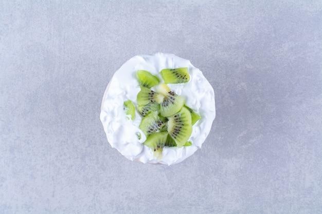 Crème glacée dans un socle en verre avec des tranches de kiwi sur une table en marbre.