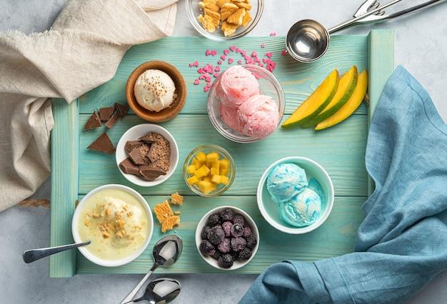 Crème glacée de différents types, fruits et baies congelées sur un mur bleu clair. vue de dessus, horizontale.