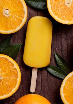 Crème glacée à l'orange et aux fruits frais avec des feuilles d'oranges fraîches sur fond de bois.