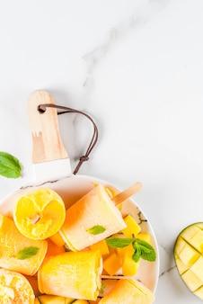 Crème glacée, sucettes glacées. aliments diététiques biologiques, desserts. smoothie mangue surgelé, avec des feuilles de menthe et de mangue fraîche, sur une plaque, sur une table en marbre blanc. vue de dessus du fond