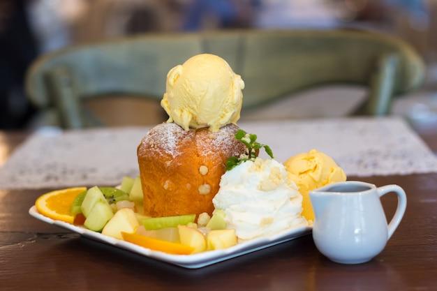 Crème glacée sucrée avec des fruits tranchés sur une table en bois, mélange de fruits et de la crème glacée