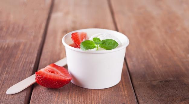 Crème glacée à la vanille avec gaufres, feuille de menthe, fraises et myrtilles sur la table en bois