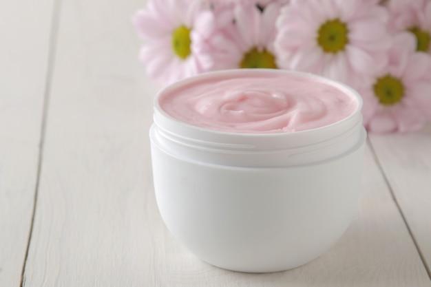 Crème en gros plan d'un pot blanc et fleurs de chrysanthème sur une table en bois blanc.