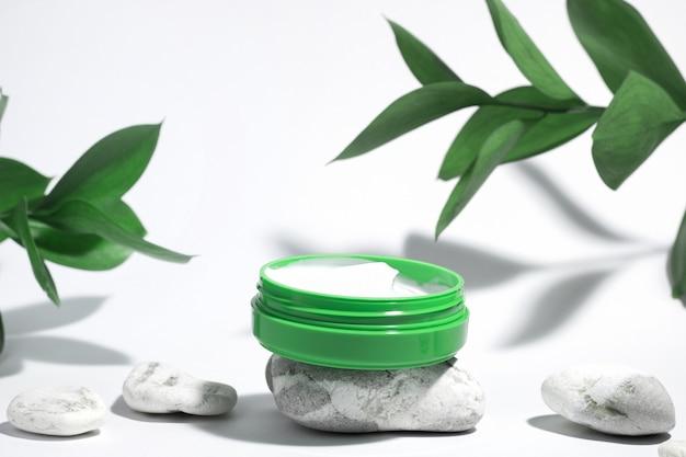 Crème hydratante cicatrisante pour le visage dans un récipient vert isolé