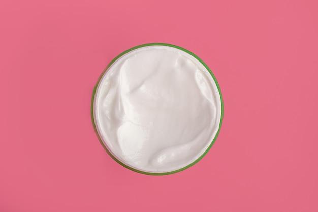 Crème hydratante cosmétique visage blanc dans un pot rond sur fond rose. mise à plat macro isolée.