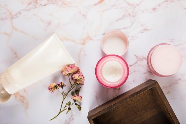 Crème hydratante avec des fleurs sur fond de marbre