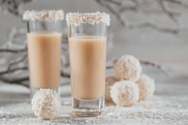 Crème irlandaise ou liqueur de café avec des boules saines de noix de coco maison et des flocons de coco sur fond clair