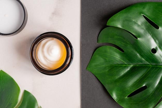 Crème de jour hydratante sur une surface en marbre. décoration de feuilles de monstera grean