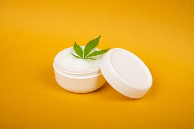 Crème de marijuana naturelle de cosmétiques de cannabis et feuille verte sur le fond jaune de beauté