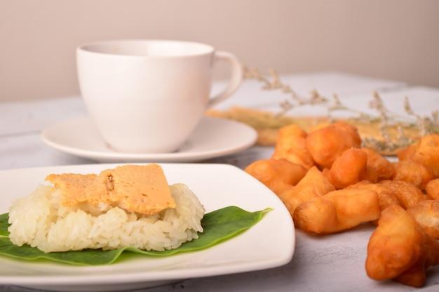 Crème d'oeuf dessert thaïlandais avec du riz gluant sur une feuille de banane avec une pâte frite