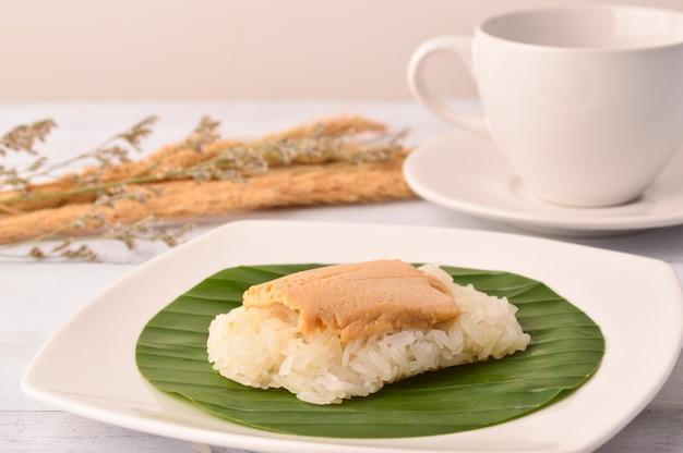 Crème d'oeuf dessert thaïlandais avec du riz gluant sur une feuille de bananier