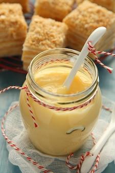 Crème pâtissière dans un bocal en verre avec une cuillère en céramique blanche
