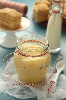 Crème pâtissière en pot de verre sur un fond en bois bleu