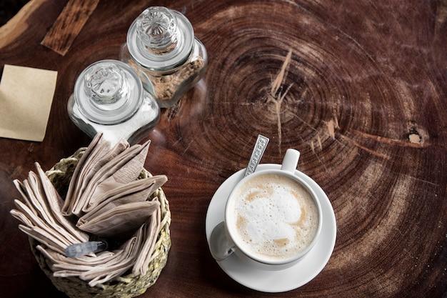 Crème pour café ou thé avec une tasse de café et une tasse de thé avec du papier de soie et du sucre sur la table en bois