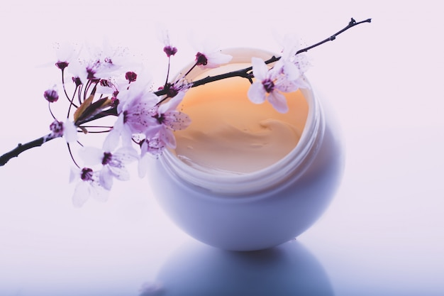 Crème pour le corps et fleurs sur fond clair