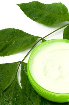 Crème pour le visage avec une feuille verte sur fond blanc